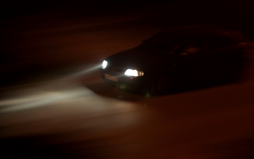Car going fast in the night, rays of light from the headlights
